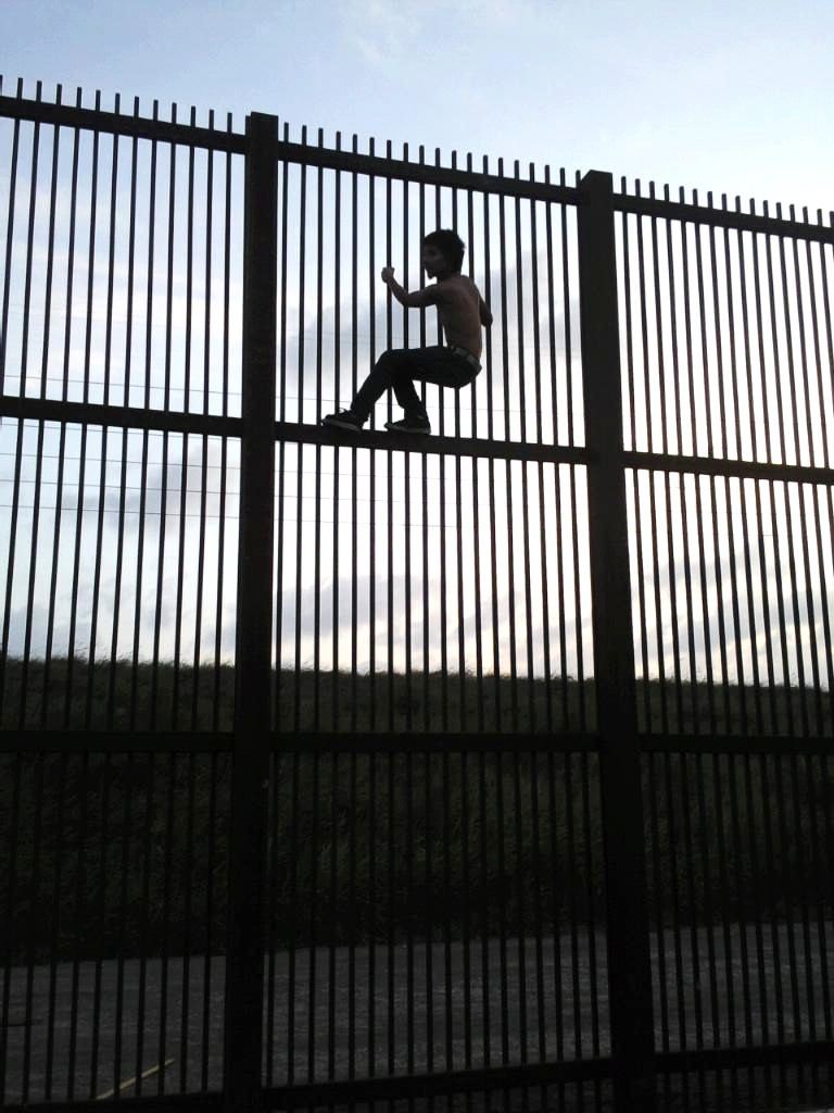 A child climbing a fence at mexico us border jewish for Border wall