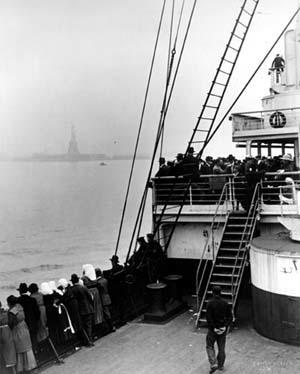 Photo of immigrants on boat looking at the statue of liberty