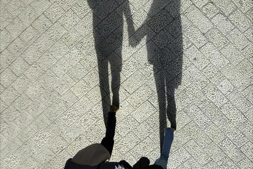 Couple and their shadows holding hands photo
