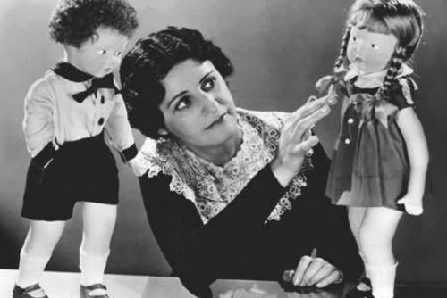 Beatrice Alexander examining two dolls