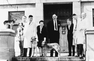 Gertrude Elion at Harvard Medical School with Dr. Roy Calne, Dr. George Hitchings, Dr. Donald Searle, Dr. Hager, and Dr. Joseph, Murray, and the dogs Tweedledum, Tweedledee, Titus, and Lollipop (recipient of the first successful foreign kidney transplant)