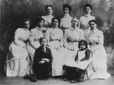 "The ""Henry Street Family"": (back row, left to right) Jane Hitchcock, Sue Foote, Jeannne Travis; (middle row) Mary Magoun Brown, Lavina Dock, Lillian Wald, Ysabella Waters, Henrietta van Cleft; (in front) 'Little Sammy' Brofsky and 'Florrie' Long"
